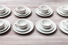Kilka biali spodeczki na szarym brązu stole i filiżanki Zdjęcia Stock