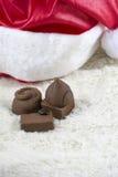 Kilka czekoladowi cukierki z bożymi narodzeniami kapeluszowymi na białym futerku Zdjęcia Stock