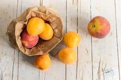 Kilka dojrzali peachs w Kraft i morele zdosą Zdrowy eatin Zdjęcie Royalty Free