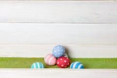 Kilka Easter jajek kolorowy handmade kłamstwo na stosie na zielonym gazonie przeciw drewnianemu nawierzchniowemu tłu Fotografia Royalty Free