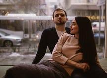 kilka kocha? Facet i jego dziewczyna siedzi blisko do each inny na windowsill wewn?trz ubierali?my wewn?trz w pulowerach i cajgac obraz stock