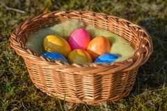 Kilka kolorowi Wielkanocni jajka w koszu na trawie zdjęcie stock