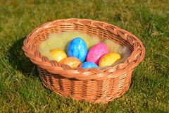 Kilka kolorowi Wielkanocni jajka w koszu na trawie fotografia royalty free
