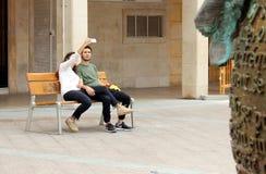 Kilka młodzi ludzie siedzi na ławce bierze obrazek one z telefonem komórkowym obrazy stock