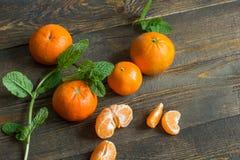 Kilka mandarynek pomarańcze na drewnianym tle Obraz Stock
