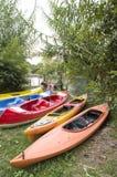 Kilka pojedynczy i dwoiści kajaki na brzeg rzeki Zdjęcie Stock
