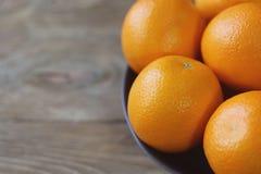 Kilka pomarańcze są jaskrawym pomarańcze w popielatym pucharze na starym drewnianym tła zbliżeniu Zdjęcia Stock