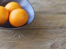 Kilka pomarańcze są jaskrawym pomarańcze w popielatym pucharze na starym drewnianym tła zbliżeniu Fotografia Royalty Free