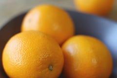 Kilka pomarańcze są jaskrawym pomarańcze w popielatym pucharze na starym drewnianym tła zbliżeniu Obraz Stock