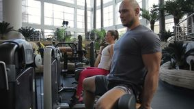 Kilka sportspeople pociągi ich nogi obsiadanie przed prasową maszyną w gym zbiory wideo