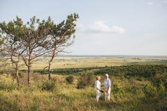 Kilka starsi dorosli w białej pościeli sukni stoją outdoors, w rękach bukiet kwiaty, trzy fotografia royalty free