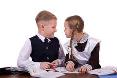 Kilka szkoła podstawowa ucznie siedzą przy biurkiem Obraz Royalty Free