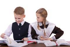 Kilka szkoła podstawowa ucznie siedzą przy biurkiem Obrazy Royalty Free