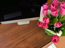 Kilka tulipany na drewnianym praca stole z monitorem i odbiciami zdjęcie royalty free