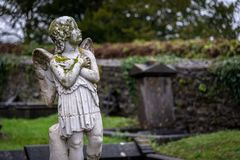 KILKENNY, IRELAND, DECEMBER 23, 2018: Sculpture of an old creepy cherub angel in the middle of a graveyard, full of lichen and