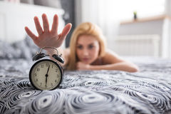 Kill the alarm clock. A photo of young woman lying on bed and managing to turn off the alarm clock royalty free stock images