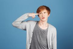 Kill me please. Young good-looking tired male student with ginger hair in casual gray outfit making gun gesture with Royalty Free Stock Photo
