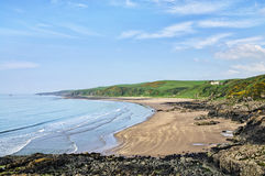 Killantringan Bay in Dumfries and Galloway. Picturesque view of the curving Killantringan Bay in Dumfries and Galloway, Scotland, with  waves breaking onto the Stock Images