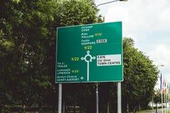 Killarney, Ιρλανδία - οδικά σημάδια στο N22 δρόμο στο Κορκ, Mallow, Kenmare, Tralee, το πεντάστιχο, και τον αερολιμένα ιρλανδικών Στοκ Εικόνες