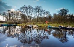 Killarney national Park canal boats. Small fishing boats reflected in the canal, Killarney national Park Stock Photo