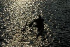 Kille som paddlar en utriggarekajak av in i solnedgången royaltyfri fotografi