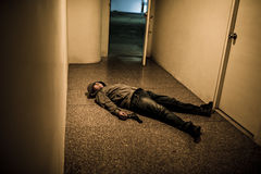 Killed gangster. Lying on the floor in corridor Royalty Free Stock Image