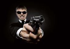 Killer. Portrait  the  beautiful  man in black costume,  special-service agent or  body guard with  pistol Royalty Free Stock Photo