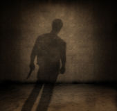 Killer. Shadow of a man with a knife in a dark grungy room royalty free stock image
