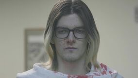 Killer in blood looks at camera. Stock. Young man with downcast eyes and glasses is splattered with blood. Devastated