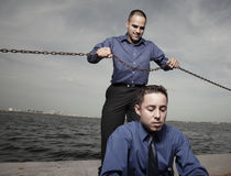Killer businessman. Image of one businessman about to choke the other businessman with a chain royalty free stock photo