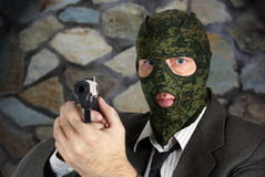 Killer in camouflage mask is aiming with a pistol Stock Images