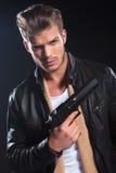 Killer in der ledernen Kleidung, die ein großes Gewehr in seiner Hand hält Stockfoto