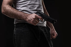 Killer with gun on black background at the studio Royalty Free Stock Image