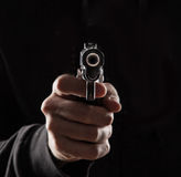 Killer with gun. Killer with gun close up over dark background stock photos