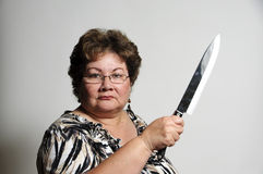 Killer look. An older Hispanic woman holding a big knife with a serious look Stock Photo