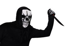 Killer with a mask. Halloween disguise - A man wearing a skull mask waving a knife Stock Image