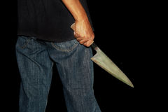 A killer person with sharp. Evil criminal with large sharp knife ready for robbery or to commit a homicide royalty free stock image
