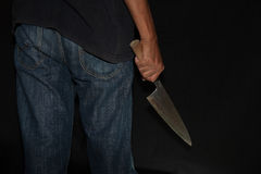 A killer person with sharp. Evil criminal with large sharp knife ready for robbery or to commit a homicide royalty free stock photo