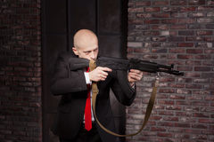 Killer in suit and red tie shoot a machine gun Stock Photos