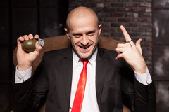 Killer in suit and tie ready to pull a grenade pin Royalty Free Stock Images