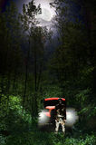 Killer in the woods. The Moon bright above the forest at night, illuminating a frightening man with a bloody machete, close to an rusty old car with the lights Royalty Free Stock Photo