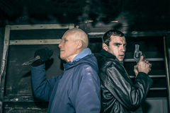 Killers. Two dangerous armed men with gun and knife standing in old dark cabin stock image