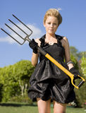 Killing Weeds With Killer Style. Woman Standing In Her Front Garden Looking Stunning In A Black Dress Holing Gardening Pitchfork Killing Weeds With Killer Style Royalty Free Stock Image