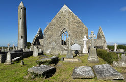 Kilmacduagh monastery with stone tower in Ireland. Royalty Free Stock Photography