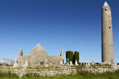 Kilmacduagh monastery with stone tower in Ireland. Stock Image