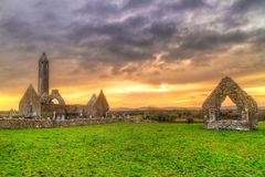 Kilmacduagh monastery with stone tower at sunset Royalty Free Stock Image
