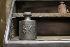 5 Kilogramm-Gewichte - alte 5-Kilogramm-Gewichte auf Werkbank Lizenzfreie Stockfotografie
