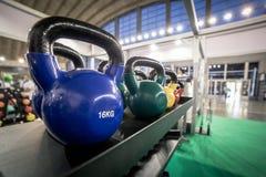 16 kilogramos Kettlebells para el ejercicio puesto en estante en gimnasio imagen de archivo libre de regalías