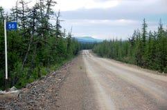 Kilometer post at taiga gravel road Stock Photography