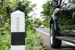A kilometer stone on the Country road with the car background. Stock Image